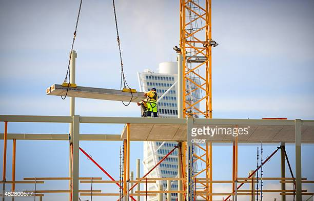 Construction workers in profile working with a crane.