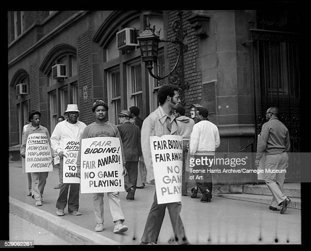 Construction workers including Roy Mellix in front demonstrating with placards reading 'Fair bidding Fair award No game playing' and 'Housing Board...