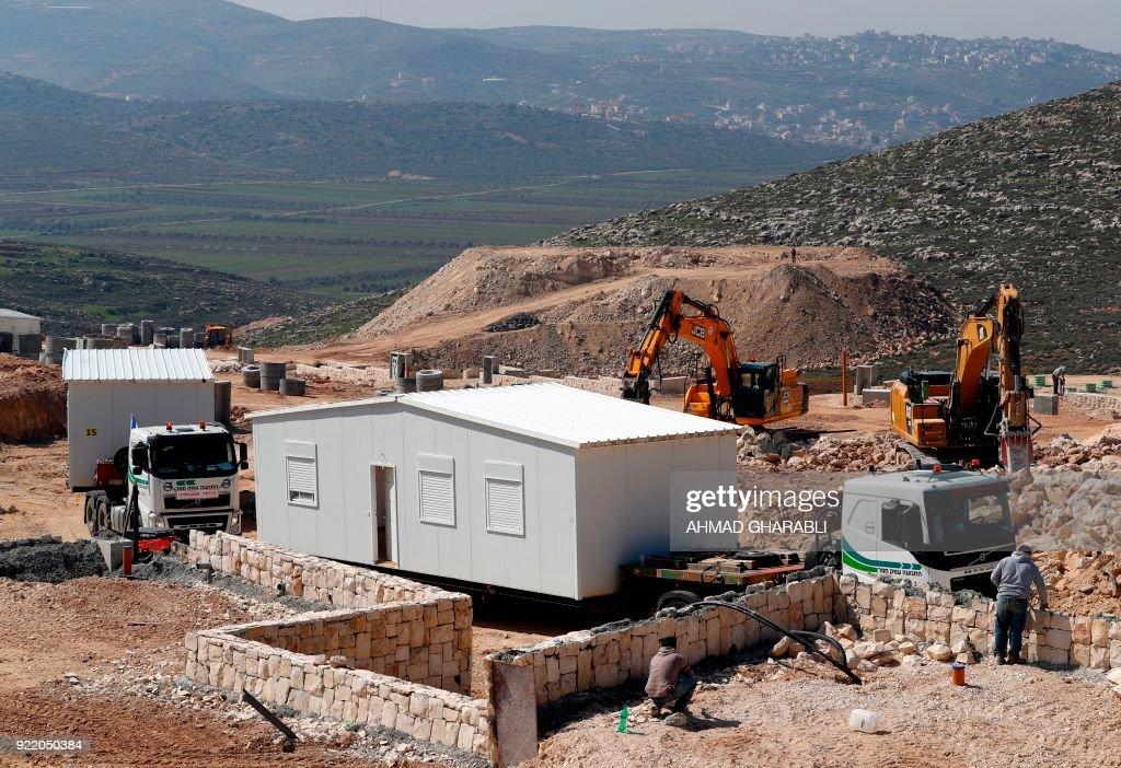 Construction workers install new mobile homes in Amichai, the first new Israeli government-sanctioned settlement built in the Palestinian territories in some 25 years, mear the settlement of Shiloh, between the Palestinian cities of Ramallah and Nablus in the Israeli-occupied West Bank, on February 21, 2018, after the Israeli government decided to relocate there the settler families evicted from the wildcat outpost of Amona. /