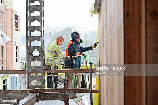 Construction workers install protective membrane