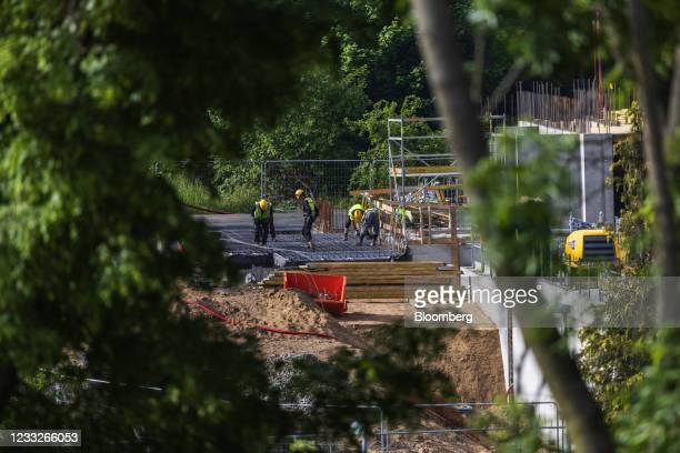 Construction workers install steel reinforcement rods during ground work at a residential apartment block construction site, on a plot of brownfield...