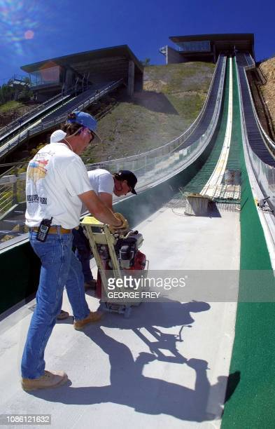 Construction workers Jay Mirci and Tim Lockington of JKM Construction grind down the lip of the K120 ski jump at the Utah Olympic Park on 15 June...