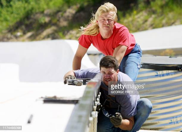 Construction workers Jim Houghtby and Kevin Foggin install a guide rail at the start of the luge and bobsleigh runs at the Utah Olympic Park in Park...