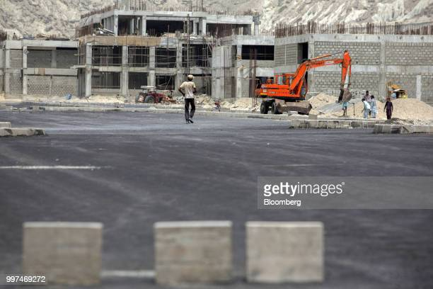 Construction workers labor at a development site operated by China Overseas Ports Holding Co near Gwadar Port in Gwadar Balochistan Pakistan on...