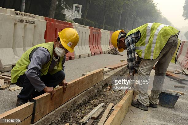 Construction workers labor by the side of a road in Singapore, on Friday, June 21, 2013. Singapore's smog hit its worst level, blanketing the...