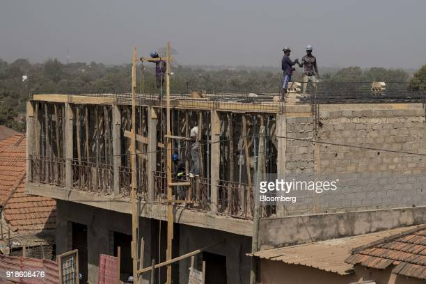 Construction workers labour on a building site in Bissau GuineaBissau on Monday Feb 12 2018 The International Monetary Fund said an increase in...