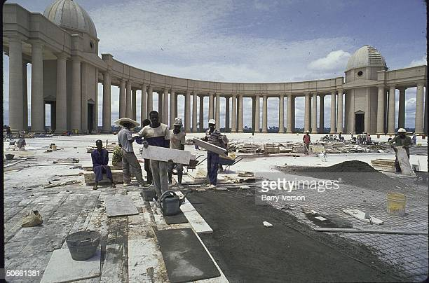 Construction workers laying marble in peristyle at St Peter'slike Basilica of Our Lady of Peace pet project of Pres Felix HouphouetBoigny
