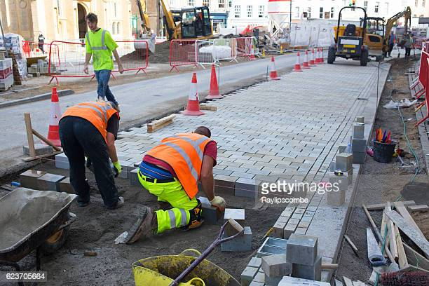 construction workers laying slabs - urban renewal stock pictures, royalty-free photos & images