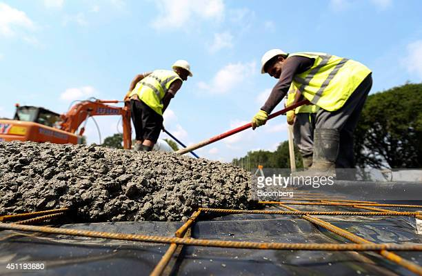 Construction workers level out freshly poured cement over the floor of a home under construction at a Crest Nicholson Holdings Plc residential...