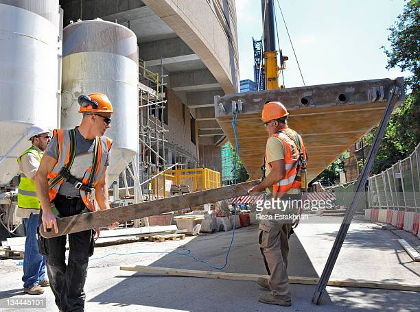 construction workers lift steel truss - construction industry stock pictures, royalty-free photos & images