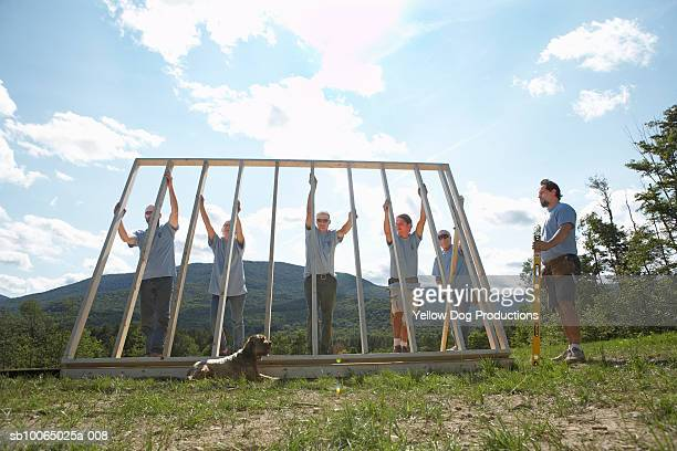 Construction workers lifting up wooden frame of house