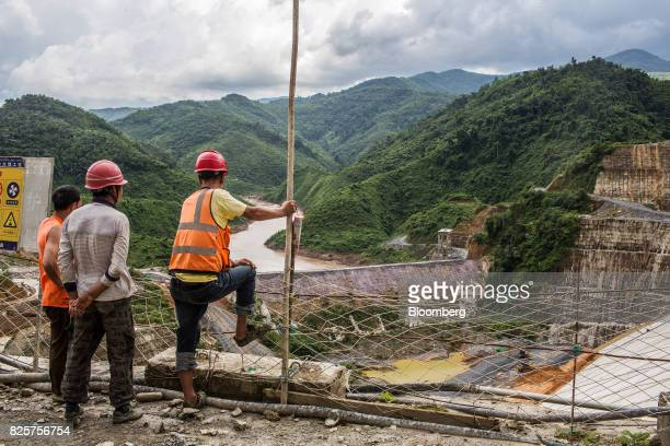 Construction workers look out over the Nam Tha 1 hydroelectric dam construction site being built by Power Construction Corp of China Ltd and to be...
