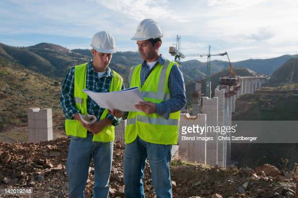 Construction workers looking at blueprint at construction site