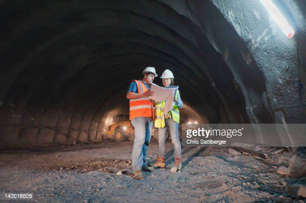Construction workers looking at blueprint in tunnel