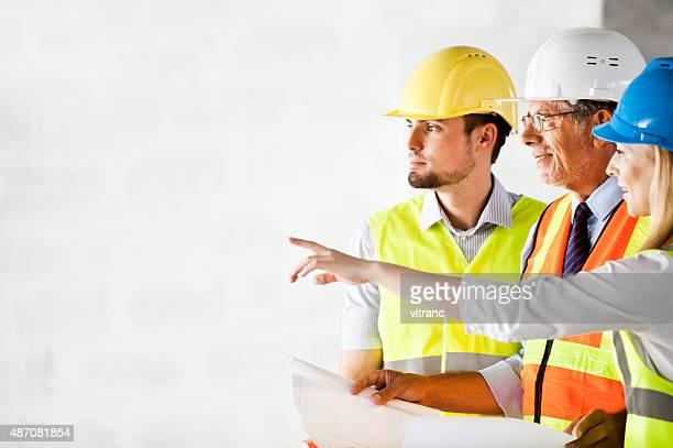 Bau Arbeiter looking at-blueprint auf Baustelle