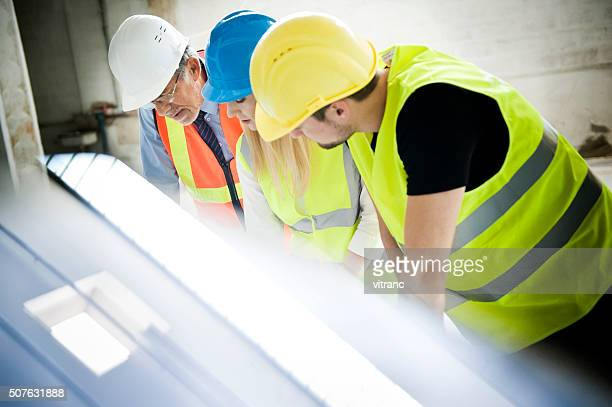 Construction workers looking at blueprint on construction site
