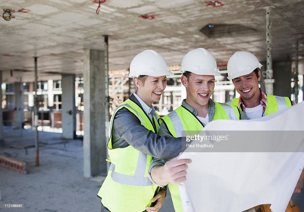 Construction workers looking at blueprints on construction site : Stock Photo