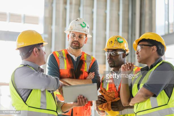 construction workers looking at digital tablet - construction industry stock pictures, royalty-free photos & images