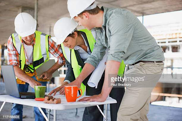Construction workers looking at papers on construction site