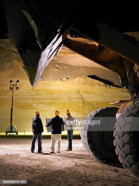 Construction workers looking at plans in sand mine at night