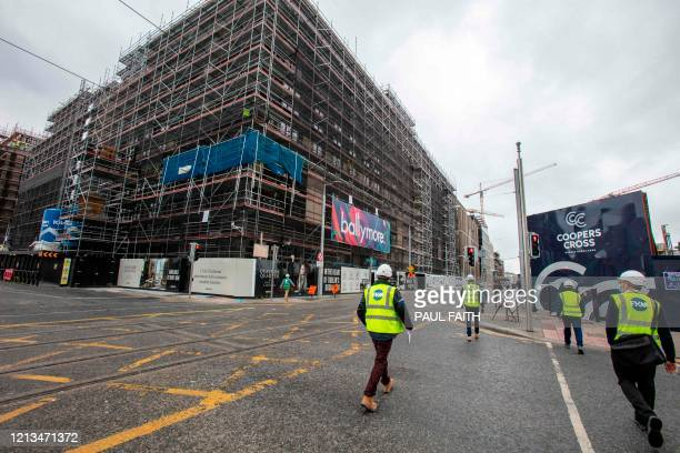 Construction workers make their way to a site along the Quays in Dublin City centre in Ireland on May 18 as Ireland cautiously begins to lift it's...