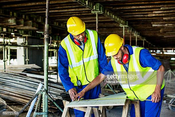 Construction workers measuring plank at site