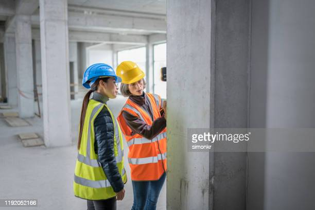 construction workers measuring support beam - coat stock pictures, royalty-free photos & images