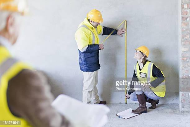 Construction workers measuring wall