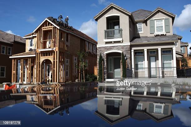 Construction workers move roofing tiles onto the roof of a newly built home in a housing development February 16 2011 in Dublin California New home...