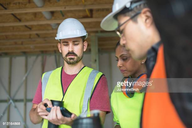 Construction workers on coffee break looking at mobile