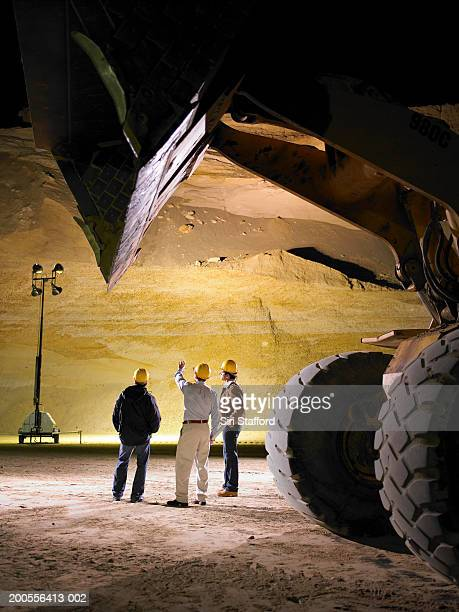 Construction workers on floor of sand mine at night