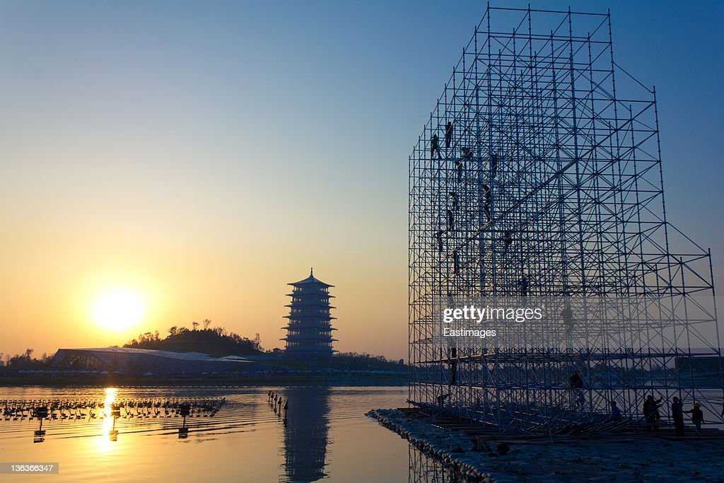 Construction workers on scaffold at sunset : Stock-Foto