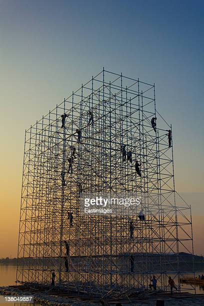 Construction workers on scaffold at sunset