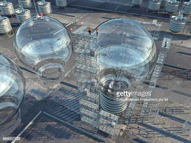 Construction workers on scaffolding at enormous light bulb