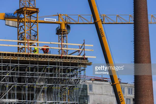 Construction workers on scaffolding beside an inactive industrial chimney at a residential apartment construction site, on a plot of brownfield land...