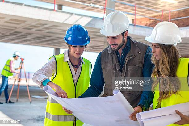 Construction workers on site working with blueprints