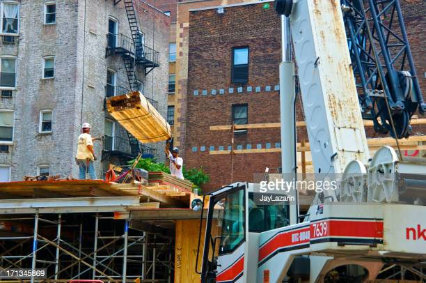 construction workers on top of scaffold, manhattan, new york city - construction platform stock photos and pictures