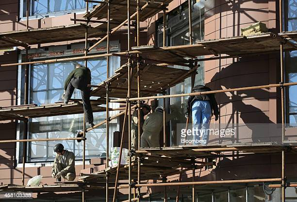 Construction workers operate on scaffolding outside a luxury residential property development in the Golden Mile district of Moscow Russia on...
