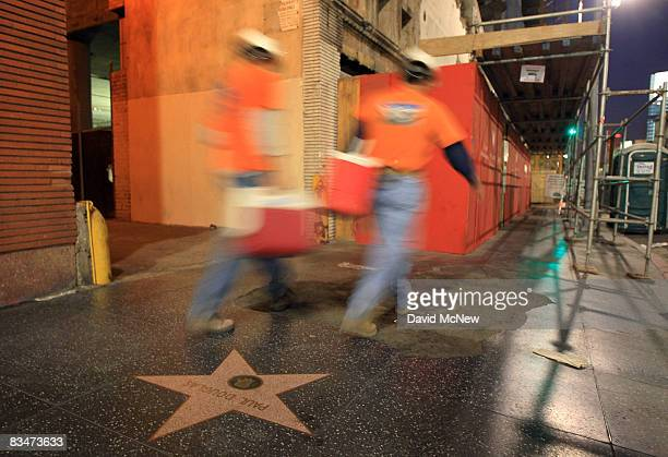 Construction workers pass over stars on the Hollywood Walk of Fame as they begin their shift at the W Hollywood Hotel & Residences project over the...