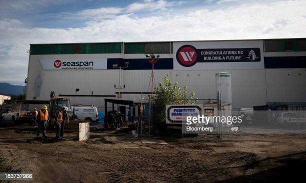 Construction workers past a building at the entrance to the Seaspan Vancouver Shipyard in North Vancouver British Columbia Canada on Wednesday Oct 9...