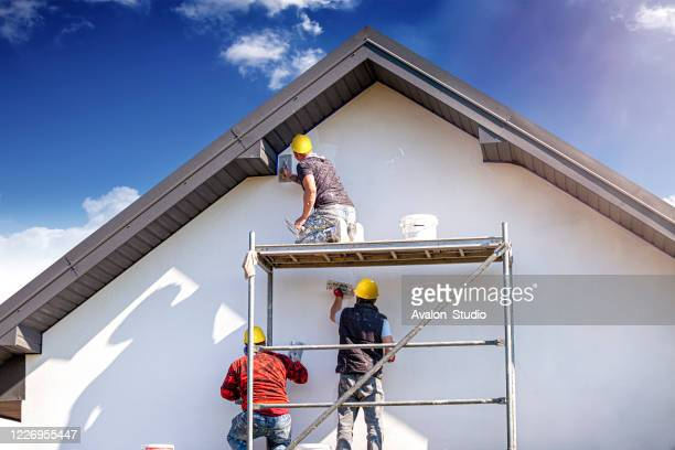 construction workers plasters the building facade. - facade stock pictures, royalty-free photos & images