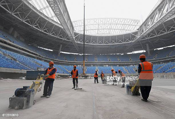 Construction workers polish the ground of the Krestovsky Stadium in Saint Petersburg during the FIFA News Agencies Tour for the FIFA Confederations...