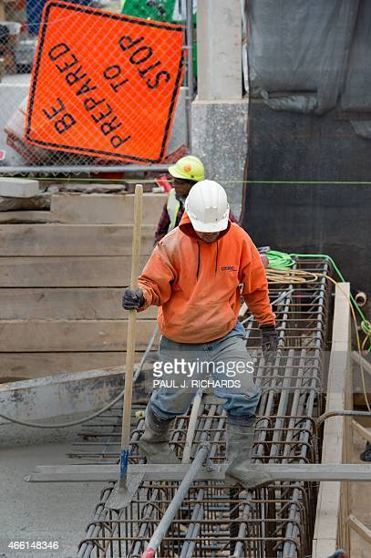 Construction workers pour concrete via a pumper truck for part of the foundation of a new building being built in downtown Washington DC on March 13...