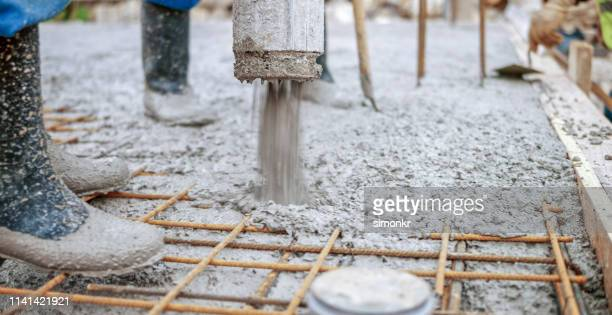 construction workers pouring cement on roof - pouring stock pictures, royalty-free photos & images