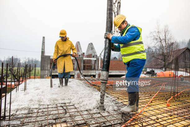 construction workers pouring cement on roof - construction material stock pictures, royalty-free photos & images