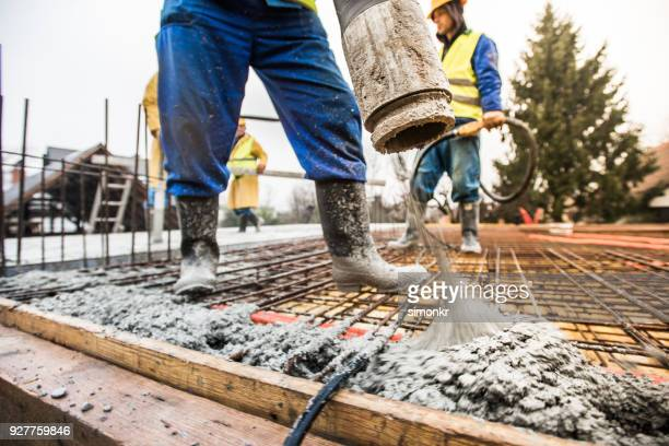 construction workers pouring cement on roof - concrete stock pictures, royalty-free photos & images