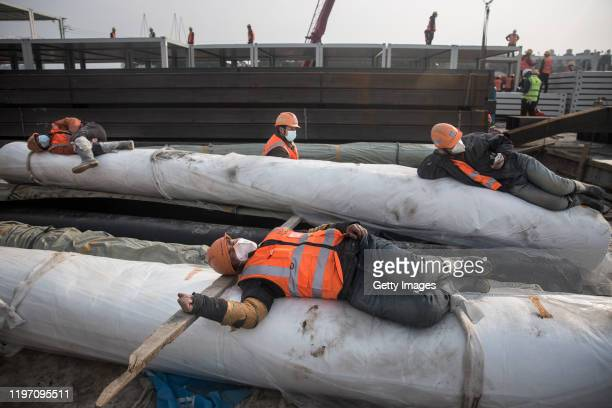 Construction workers rest on building materials as new hospitals are built to tackle the coronavirus on January 28 2020 in Wuhan China Wuhan...