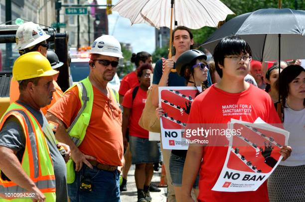 Construction workers see how a group participating in an Abolish ICE protest marches on Market Street in Center City Philadelphia PA on August 4 2018