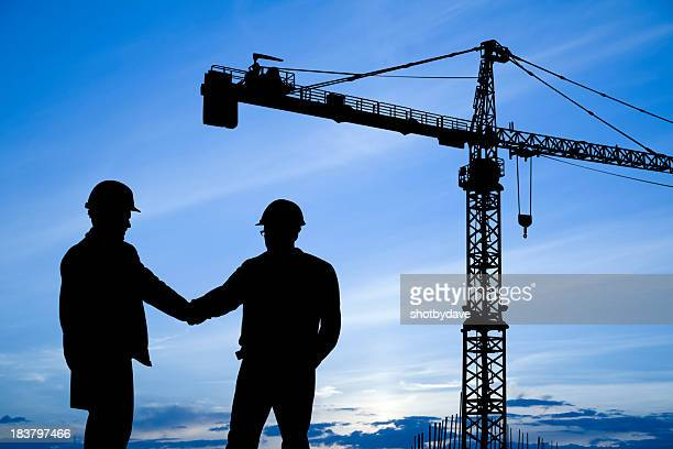 Construction workers shaking hands below crane