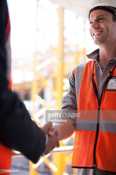 Bauarbeiter sich die Hand schütteln, auf Baustelle